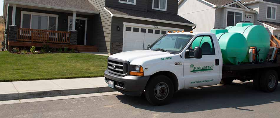 Sure Green Lawn & Tree Service, Inc. work truck preparing lawn fertilization treatment in Spokane, WA.